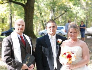Photo of Dr. Stephan J. Smith standing with Jeff and Valerie Rising after performing their wedding.