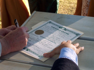 Close up photo of a marriage license being signed outdoors by a newly wedded couple.