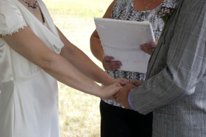 Close up photo of a couple holding hands outdoors during their wedding ceremony.