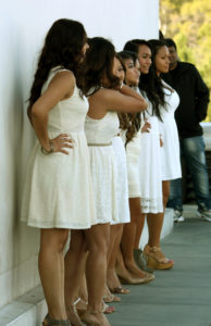 Photo of a group of bridesmaids in white dresses standing against an outdoor wall awaiting the processional.